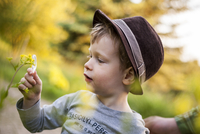 Portrait of little boy exploring nature with magnifying glass