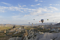 Turkey, Eastern Anatolia, Cappadocia, hot air balloons hoovering over tuff rock formations at Goereme National Park