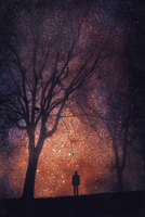 Silhouette of person in front of starry sky, composite