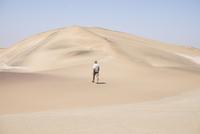 Africa, Namibia, Namib desert, Swakopmund, Dorob National Park,  guide walking on desert dune