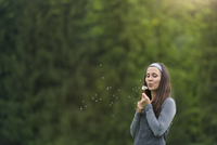 Young woman blowing blowball in front of green background 20025331077| 写真素材・ストックフォト・画像・イラスト素材|アマナイメージズ