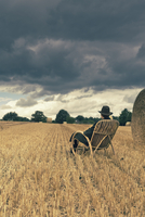 Teenage boy with hat sitting in a rocking chair on a grainfield 20025331119| 写真素材・ストックフォト・画像・イラスト素材|アマナイメージズ