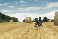 Teenage boy with hat sitting in a rocking chair on a grainfield 20025331121| 写真素材・ストックフォト・画像・イラスト素材|アマナイメージズ
