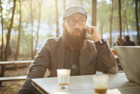 Germany, Berlin, beared man sitting in a garden cafe using smartphone