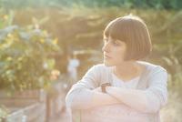 Portrait of pensive woman with bob hairdo sitting in a garden 20025331167| 写真素材・ストックフォト・画像・イラスト素材|アマナイメージズ