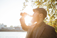 Beared man drinking beer out of a bottle at backlight
