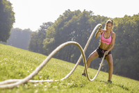 Young woman training with workout ropes on a meadow