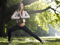 Young woman making stretching exercise on a meadow 20025331180| 写真素材・ストックフォト・画像・イラスト素材|アマナイメージズ
