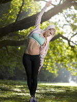 Young woman making stretching exercise on a meadow 20025331181| 写真素材・ストックフォト・画像・イラスト素材|アマナイメージズ