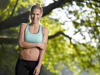 Portrait of smiling young sportswoman 20025331182| 写真素材・ストックフォト・画像・イラスト素材|アマナイメージズ