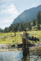 Austria, Tyrol, Tannheimer Tal, two young hikers with having a rest 20025331196| 写真素材・ストックフォト・画像・イラスト素材|アマナイメージズ