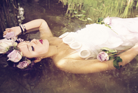 Portrait of young woman wearing wedding dress and flower crown lying in the water with closed eyes 20025331216| 写真素材・ストックフォト・画像・イラスト素材|アマナイメージズ