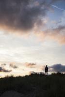 Silhouette of teenage boy standing on beach dune in front of evening twilight 20025331236| 写真素材・ストックフォト・画像・イラスト素材|アマナイメージズ
