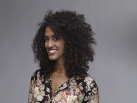Portrait of smiling young woman with nose ring and Afro in front of grey background 20025331241| 写真素材・ストックフォト・画像・イラスト素材|アマナイメージズ