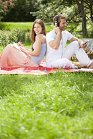 Happy couple on picnic blanket in park