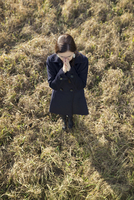 Woman with folded hands standing on a meadow