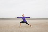 Belgium, Flanders, woman doing yoga exercises on the beach