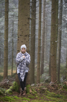 Austria, sad female teenager leaning at tree trunk in autumn