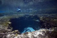 USA, Florida, Santa Fe River, scuba diver at entrance to Devil's Eye cave