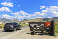 USA, Yellowstone National Park Sign at entrance, car on road