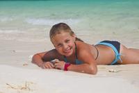 Tanzania, Zanzibar Island, portrait of girl lying on the beach at seafront