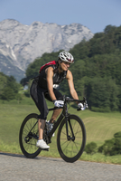 Germany, Marktschellenberg, sportive woman riding bicycle 20025331413| 写真素材・ストックフォト・画像・イラスト素材|アマナイメージズ