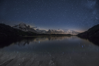 France, Mont Blanc, Lake Cheserys, Milky way and Mont Blanc reflected in the lake by night