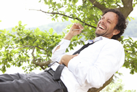 Germany, relaxed businessman lying in tree smoking a joint 20025331477  写真素材・ストックフォト・画像・イラスト素材 アマナイメージズ