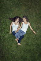 Two sisters lying on a meadow with closed eyes