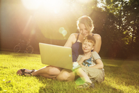 Mother and little son sitting on a meadow with laptop