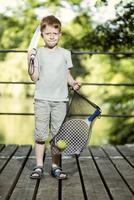 Portrait of little boy holding tennis racket and a bag 20025331515| 写真素材・ストックフォト・画像・イラスト素材|アマナイメージズ
