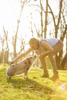 Woman taming piglet in park 20025331540| 写真素材・ストックフォト・画像・イラスト素材|アマナイメージズ