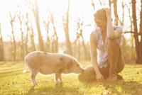 Smiling woman sitting with piglet in park 20025331542| 写真素材・ストックフォト・画像・イラスト素材|アマナイメージズ