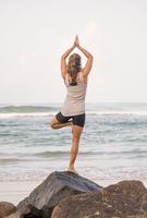 Sri Lanka, Kabalana, young woman practicing yoga at the coast