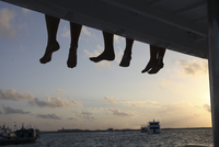 Maledives, South Male Atoll, legs of three people sitting on a jetty at evening twilight 20025331555| 写真素材・ストックフォト・画像・イラスト素材|アマナイメージズ