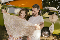 Couple looking at map in front of van in the nature