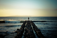 Spain, Canary Islands, Tenerife, back view of child standing at pier looking at the sea