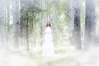 Young woman wearing white dress in the forest