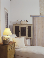LIVING ROOM - reading corner with set of three antique birdhouses, shorebird folk art decoy, shutter hung on wall, white chaise