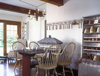 EATING AREAS: Kitchen eating area, antiques. Windsor chairs, exposed beams, white walls, wooden floor, distressed cabinet holds