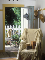 ENTRANCEWAYS: Converted garage, covered wingchair, stacks of berry baskets on chair, hooks holds garden hats, blue distressed do