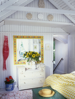 BEDROOM - Vacation home. Painted white chest, mirror with yellow frame and stylized tulips, sunflowers in white antique pitcher,