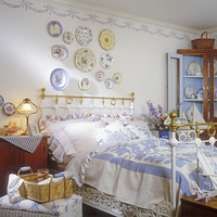 BEDROOMS: Cottage style bedroom with hanging collectible plates on wall. Stenciling border, brass bed, antique corner cupboard w