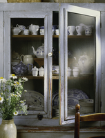 Detail of cottage chic weathered light blue grey pie safe cabinet, antique blue and white china & teapots with crock of daisies