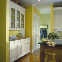 KITCHENS - View into hallway. Yellow with white custom made cabinets and trim, wood plank floor, vase of Hydranges on countertop 20025340950| 写真素材・ストックフォト・画像・イラスト素材|アマナイメージズ