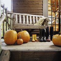 FALL SEASON: pumpkins sit on front porch with rustic handmade bench, mama papa and baby garden boots, family