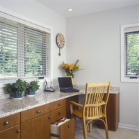 KITCHENS -Desk area, granite countertops, laptop, cordless phone, cherry wood cabinets,  vased flowers, wood blinds, bare walls,