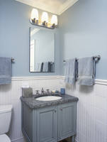 BATHROOM: Small vanity, granite counter with inset sink, tile wall up to dado, sage green paint and towels