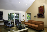 LIVING ROOMS; contemporary room with new and antique folk art , looking to sliding doors, two leather Eames chairs and ottomans,