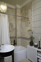 BATHROOM: Neutral tiled walls, mosaic tile beneath border, crown moulding, natural blinds, shower curtain, partial round sink, p